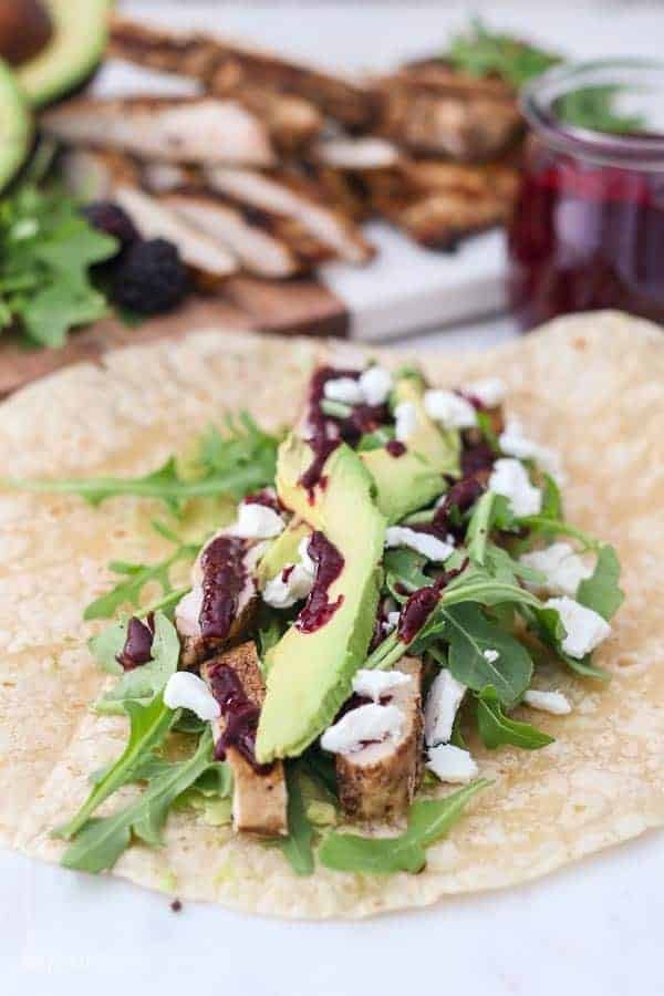 An open tortilla is filled with chicken, avocado, goat cheese, arugula and blackberry sauce