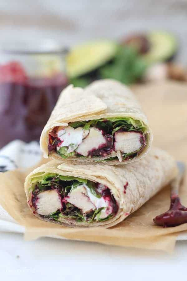 A chicken wrap is cut in half, revealing what's on the inside. Lettuce, chicken, goat cheese and an oozing blackberry sauce