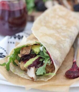 A chicken wrap is laying on a piece of brown parchment paper, hanging out of the wrap is chicken, lettuce and avocado. There's also a spoon of blackberry sauce next to it