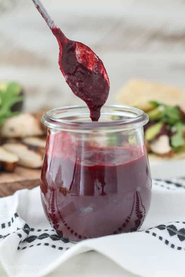 A mini spoon with blackberry sauce dripping off into the jar