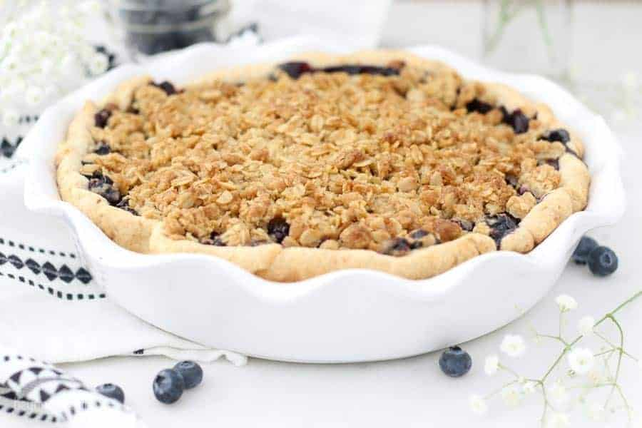 A horizontal shot of a whole blueberry pie with a crumble topping