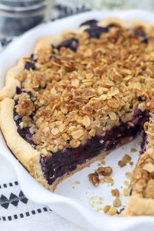 A slice is missing from a whole blueberry pie, which has the perfect crumble topping