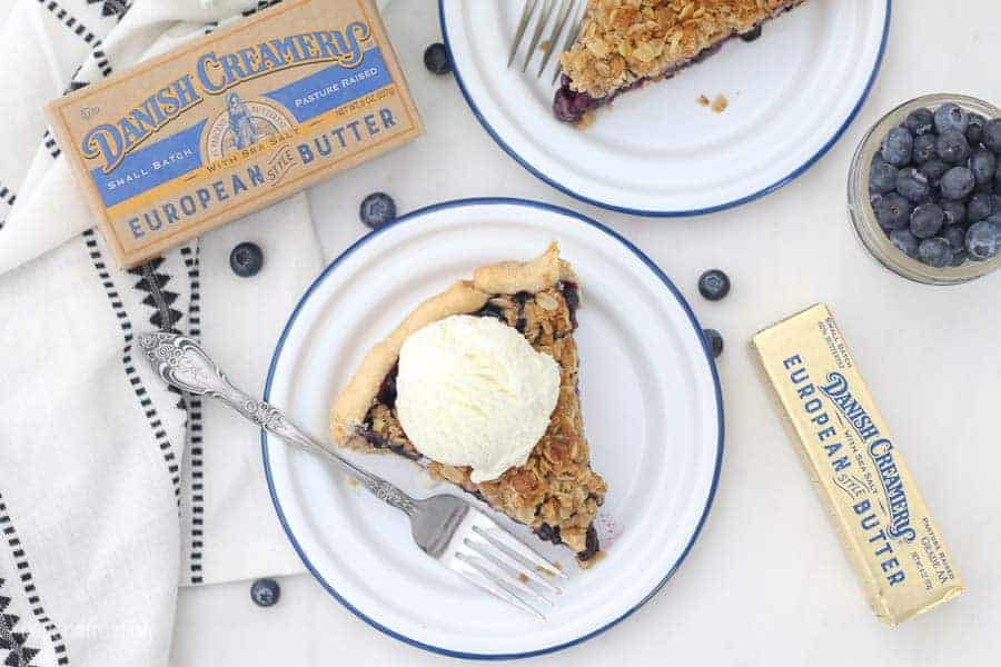 An overhead shot of a slice of pie on a white plate with a blue rim, the pie is topped with a scoop of vanilla ice cream. Scattered blueberries, and packages of danish creamery European butter surround the plate