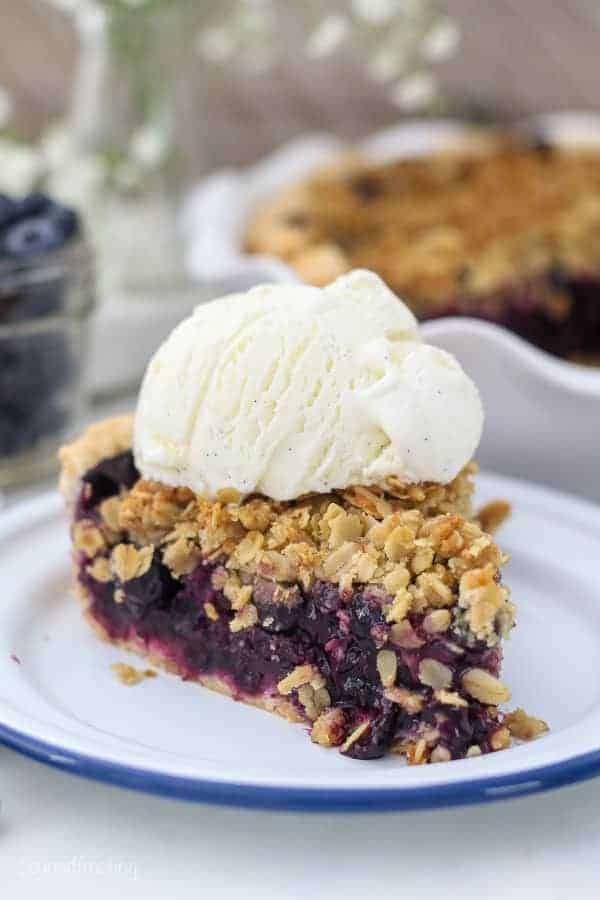 A slice of juicy blueberry pie sitting on a white plate with a blue rim, with a scoop of vanilla ice cream on top