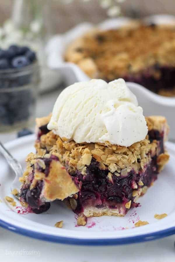 A slice of juicy blueberry pie with a couple bites missing, showing the inside of the pie with a scoop of vanilla ice cream on top. There's a fork on the plate with a bite of blueberry pie on it