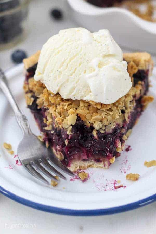 A slice of juicy blueberry pie with a couple bites missing, showing the inside of the pie with a scoop of vanilla ice cream on top