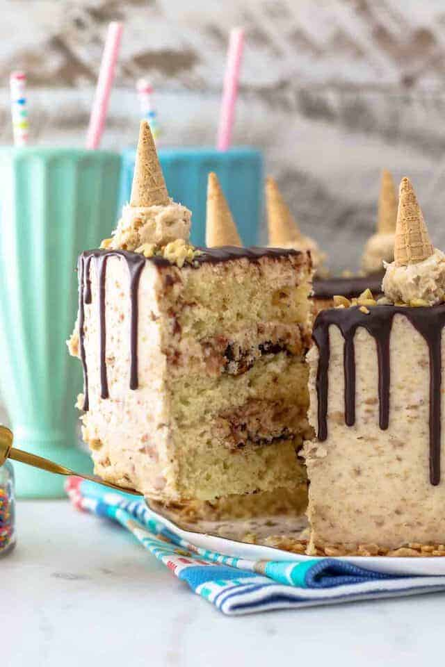 A spatula is holding a slice of layer cake called Drumstick Cake. It's got a chocolate ganache drip and mini cones