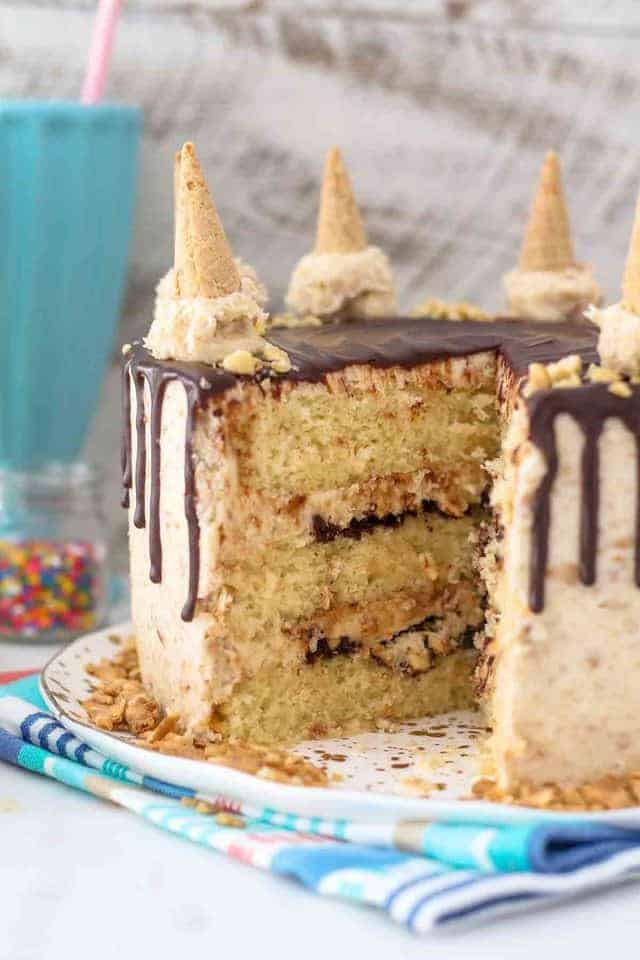 A peek inside a layered cake, the cake is covered with a chocolate ganache and mini ice cream cones