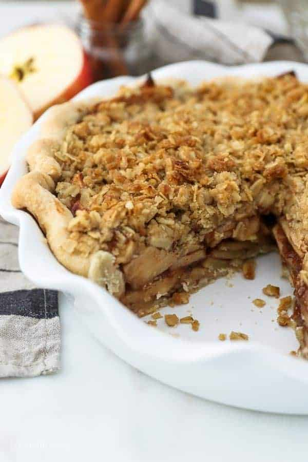 A look inside a whole apple pie with a crumble topping, one slice is missing from the pie showing all the layers of apples inside.