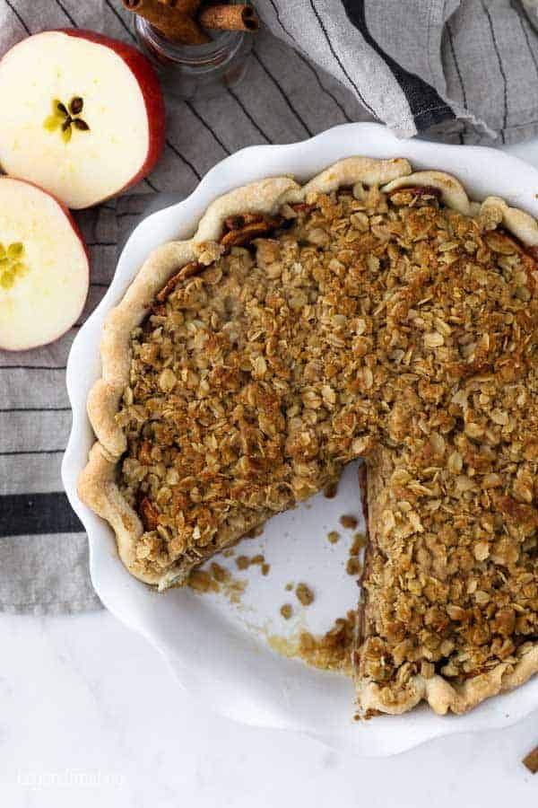 An overhead shot of pie with crumble topping, with one slice missing. There's also some sliced apples in the background and some cinnamon sticks