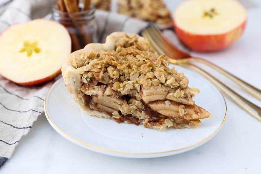 A white plate with a gold rim has a slice of apple pie with a crumble topping.