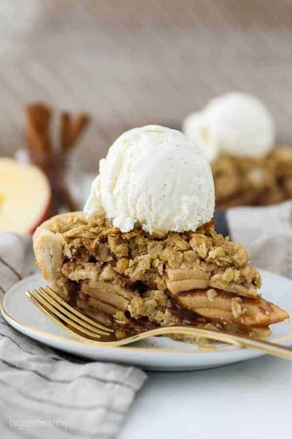 A white plate with a gold rim has a slice of apple pie with a crumble topping and a scoop of vanilla ice cream on top. There's a gold fork resting on the plate