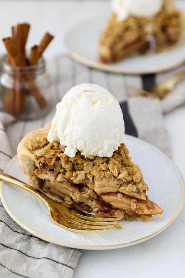 A white plate with a gold rim has a slice of apple pie with a crumble topping and a scoop of vanilla ice cream on top.