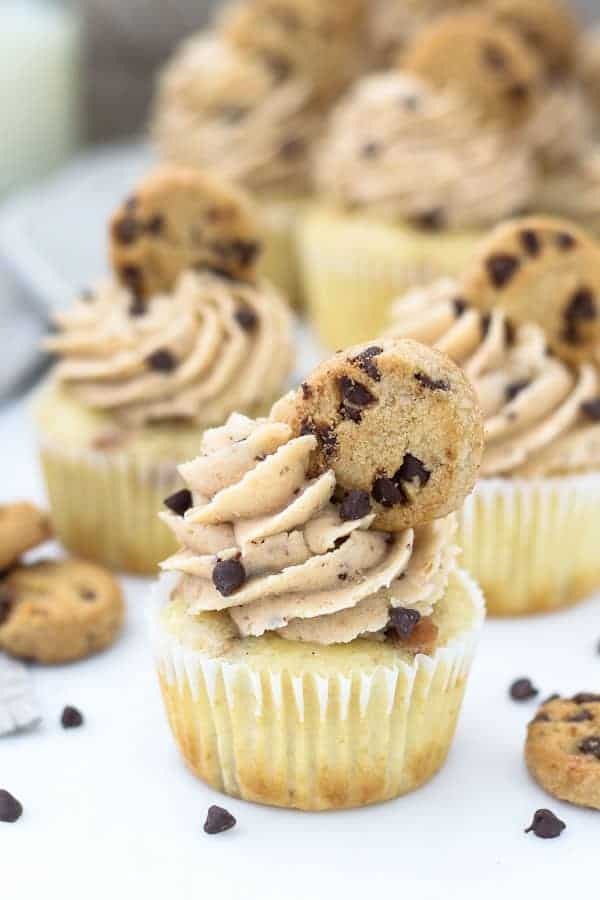 A chocolate chip cookie cupcake with a big swirl of frosting, mini chocolate chips and topped with a mini chocolate chip cookie