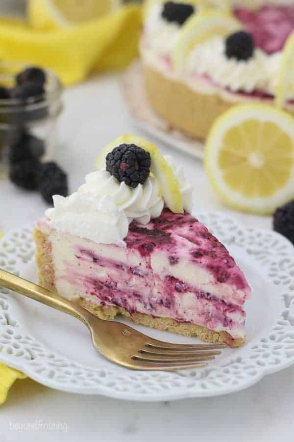 A gorgeous 3/4 view of a slice of blackberry swirled lemon cheesecake on a white plate with a gold fork sitting next to the slice of cheesecake. There's lemons and blackberries blurred out in the background