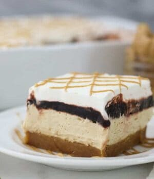 A beautiful photo of a slice of peanut butter cookie lush showing all 4 layers of the dessert. Peanut butter cookie on the bottom, peanut butter mousse, chocolate pudding and a whipped cream topping