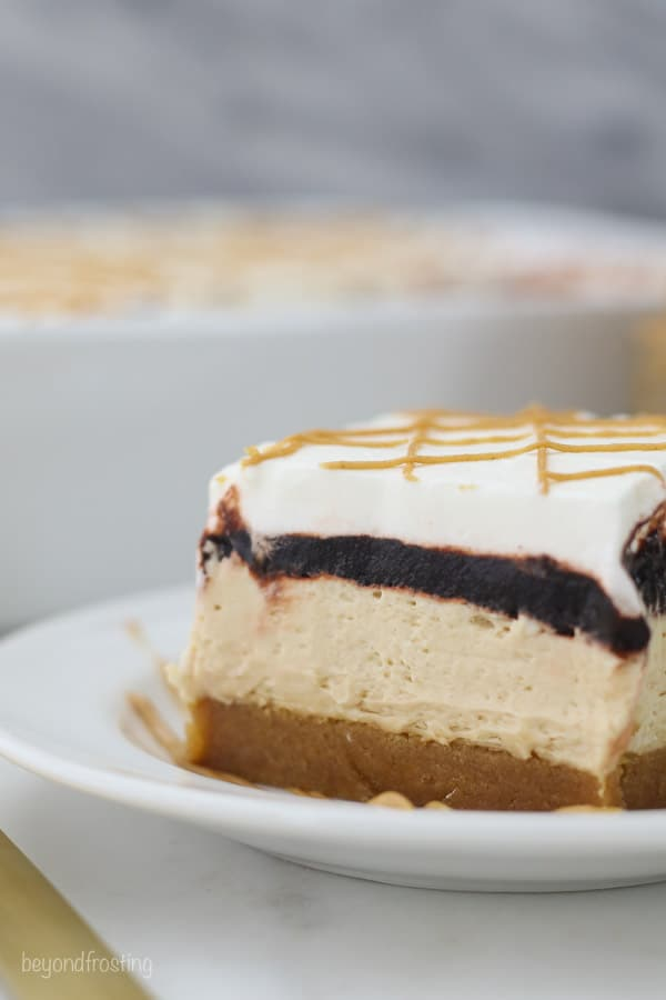A close up shot of a slice of peanut butter cookie lush showing all 4 layers of the dessert. Peanut butter cookie on the bottom, peanut butter mousse, chocolate pudding and a whipped cream topping
