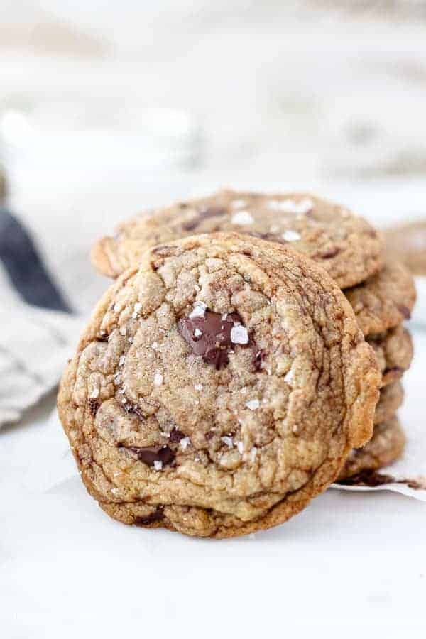 A Cookie is leaning up against a stack of other cookies. There's a big chocolate chunk on top and flaky sea salt