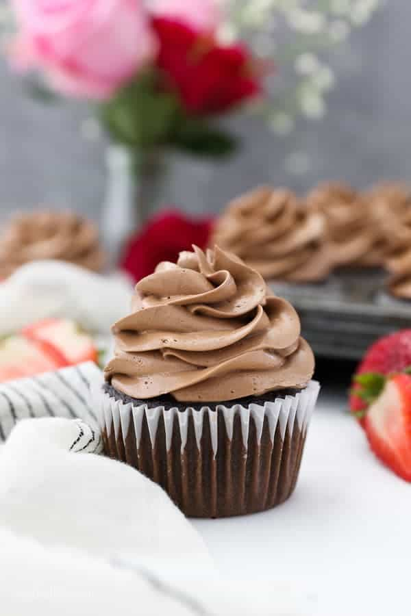 A lone chocolate cupcake frosted with a silky chocolate buttercream is surrounded by strawberries and red and pink roses.