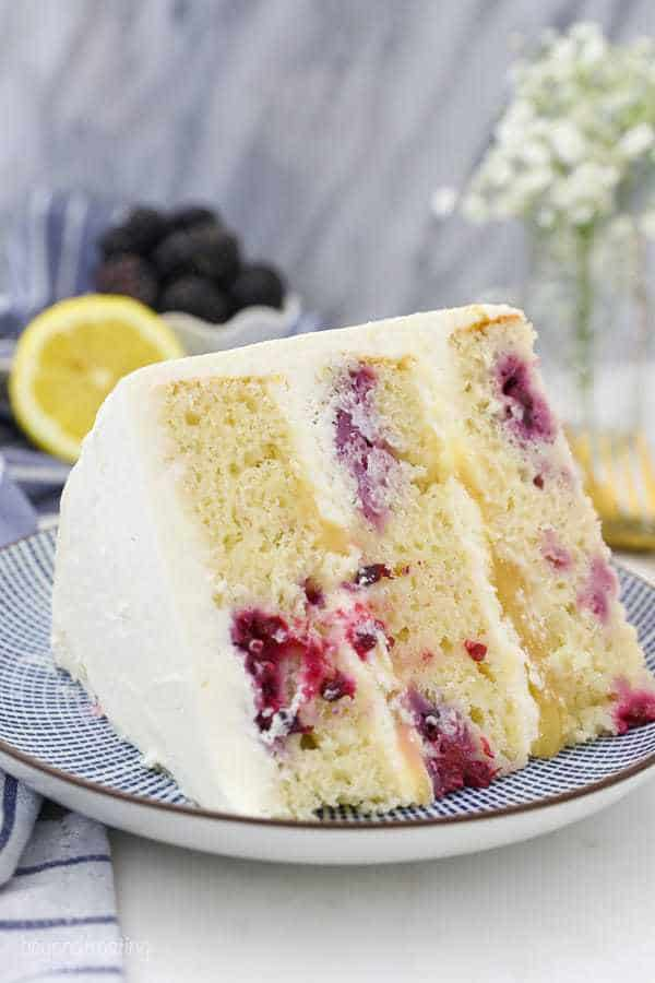 A close up shot of a lemon cake showing all the beautiful blackberries on the inside and the layers of lemon curd. The cake is sitting on a blue and white plate.