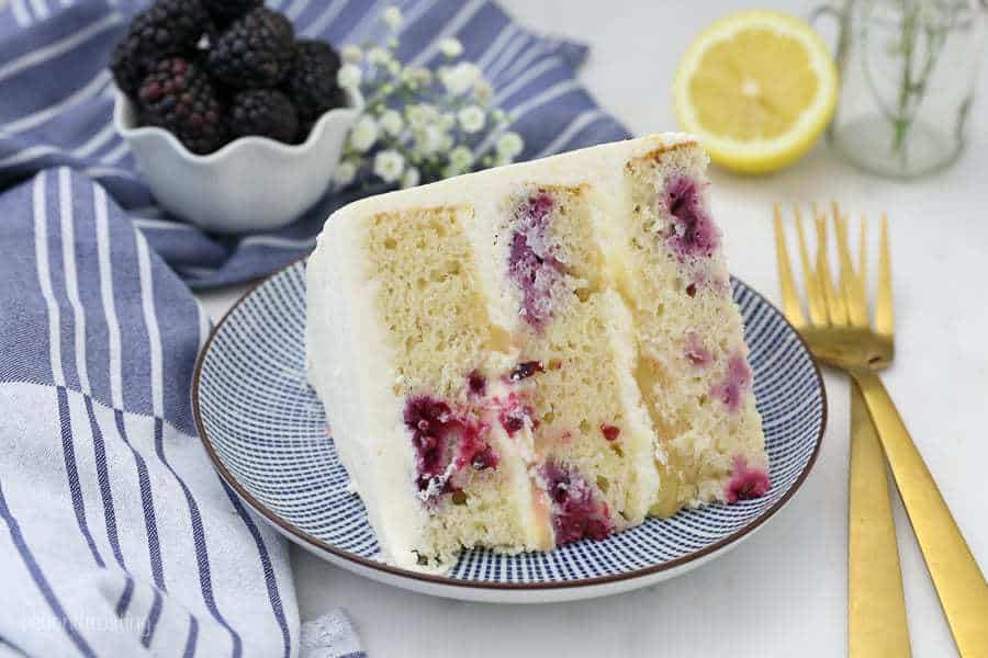 An overhead shot of a lemon cake showing all the beautiful blackberries on the inside and the layers of lemon curd .