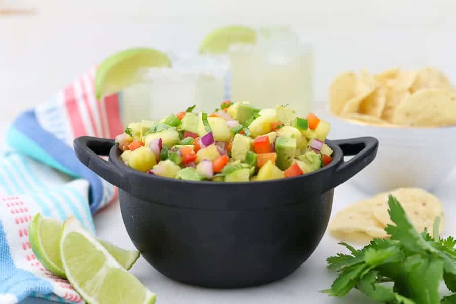 A gorgeous mini dish of pineapple salsa with some margaritas in the background and some chips and limes