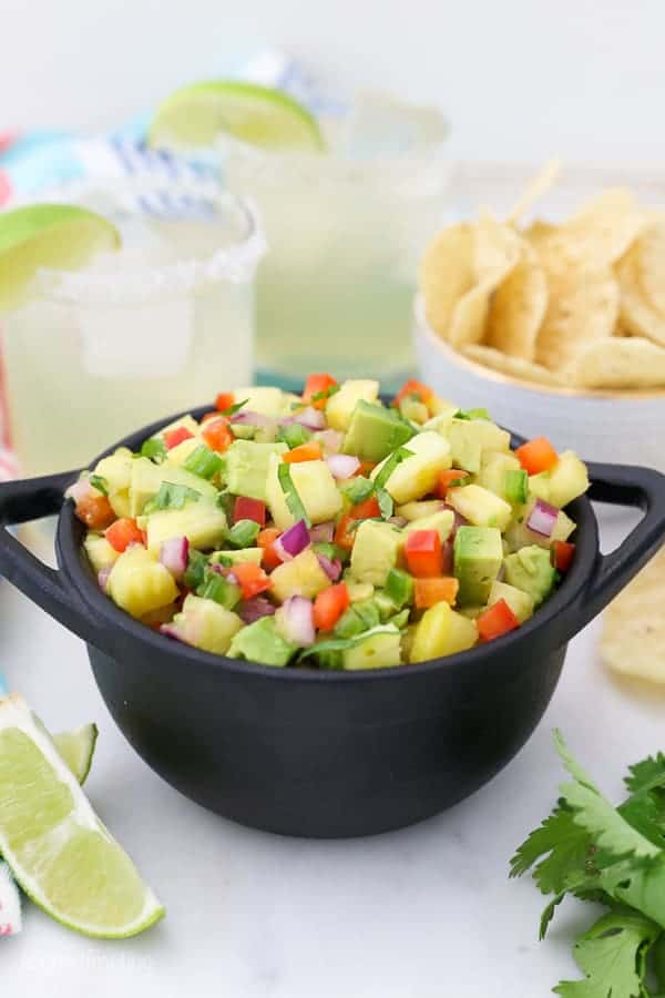 A mini cast iron dish filled with pineapple salsa and some margaritas and chips blurred out in the bkacground