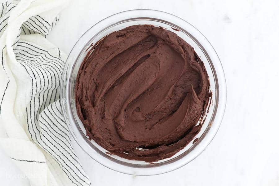 An overhead view of a glass bowl filled with chocolate frosting and a vintage napkin laid out next to it