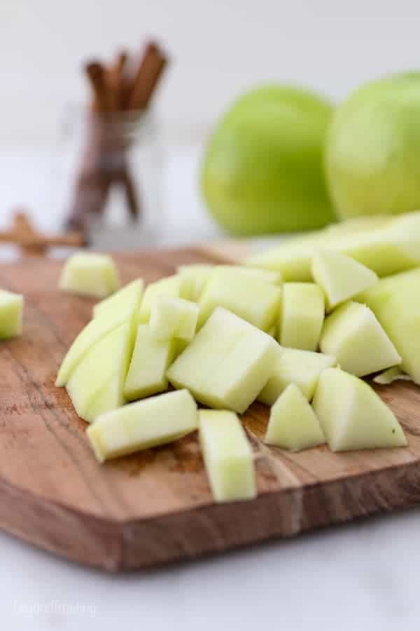 Diced green apples sitting on a wooden cutting board