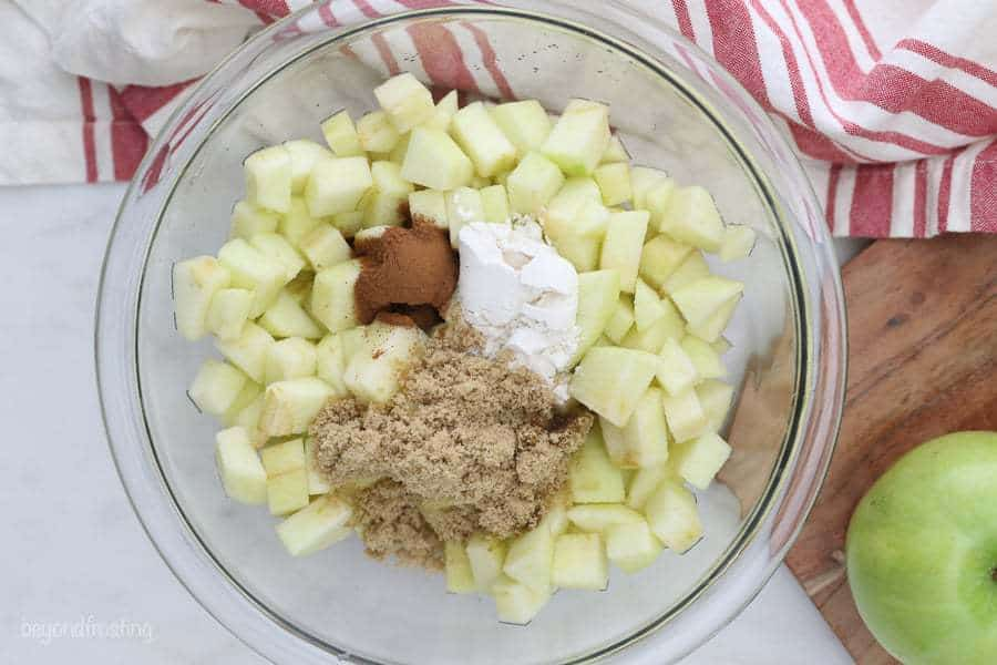 A glass mixing bowl full of diced apples, brown sugar, flour and cinnamon