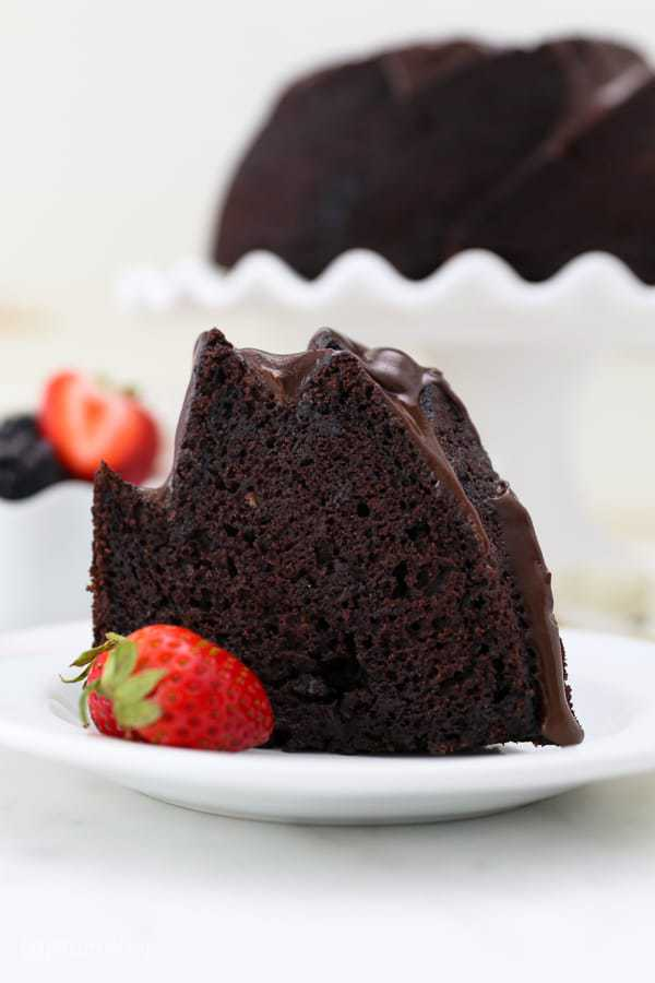 A tall slice of chocolate bundt cake on a white plate with a strawberry on the plate