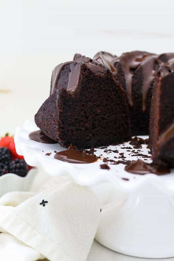 A chocolate bundt cake on a white ruffled cake plate with a couple slices missnig