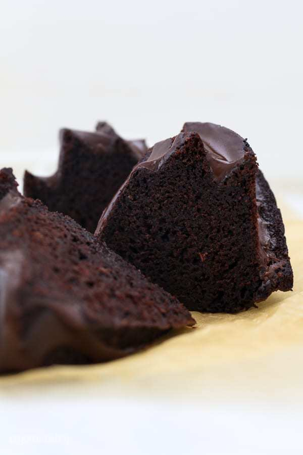 A couple slices of chocolate bundt cake laying on a piece of brown parchment paper