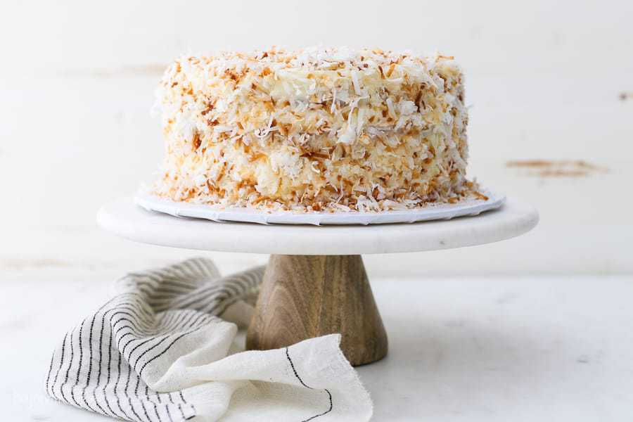 A wide shot of a coconut cake on a marble cake stand draped with a vintage stripe napkin