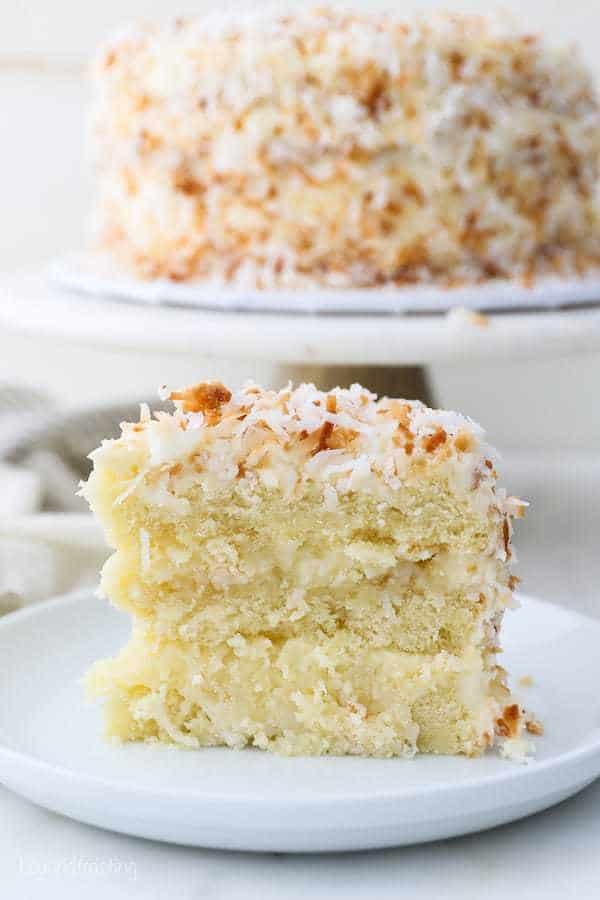 A tall slice of coconut layer cake on a white plate