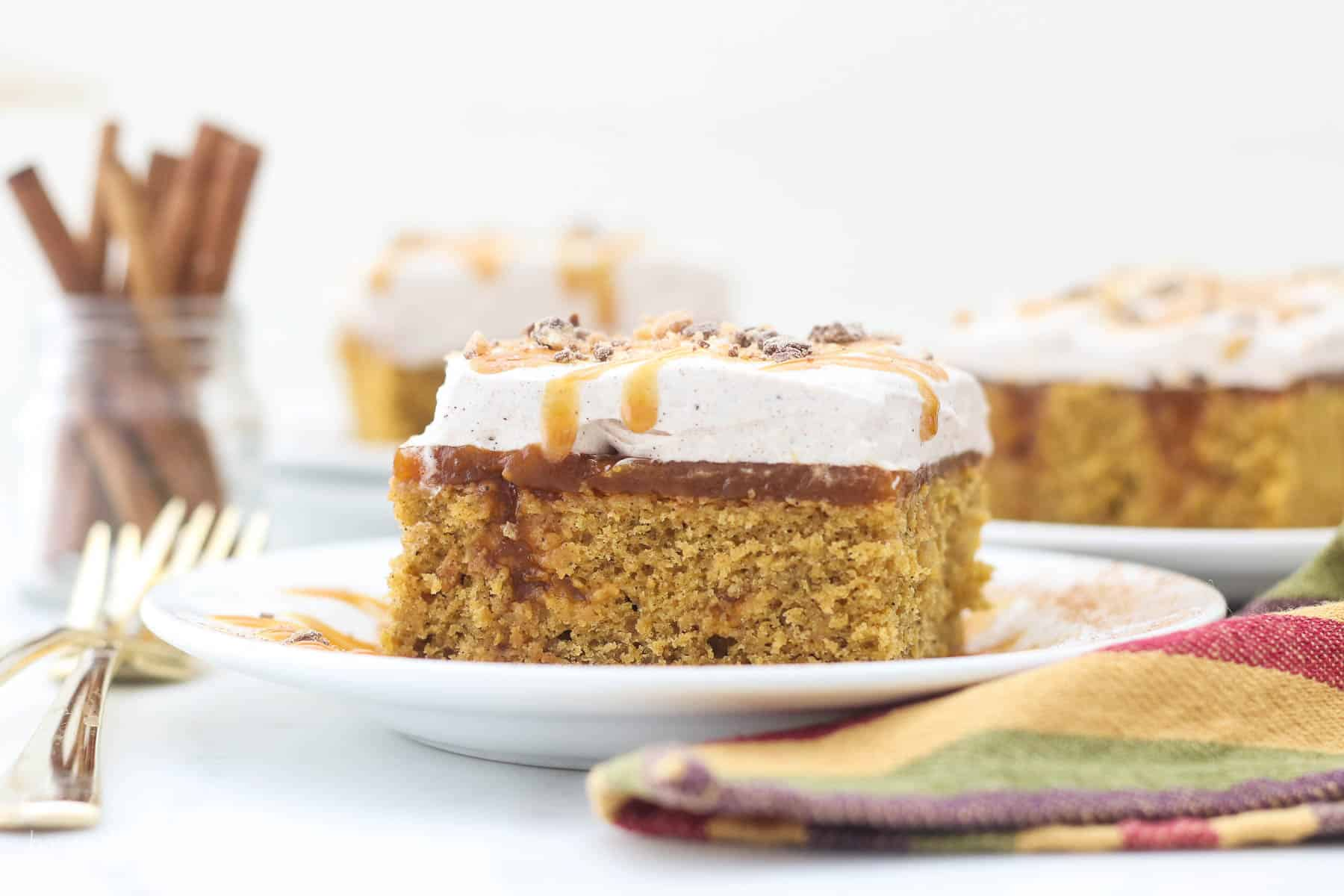A wide angle shot of a slice of pumpkin poke cake showing the layers of the cake. There's two slices blurred out in the background and some cinnamon sticks.