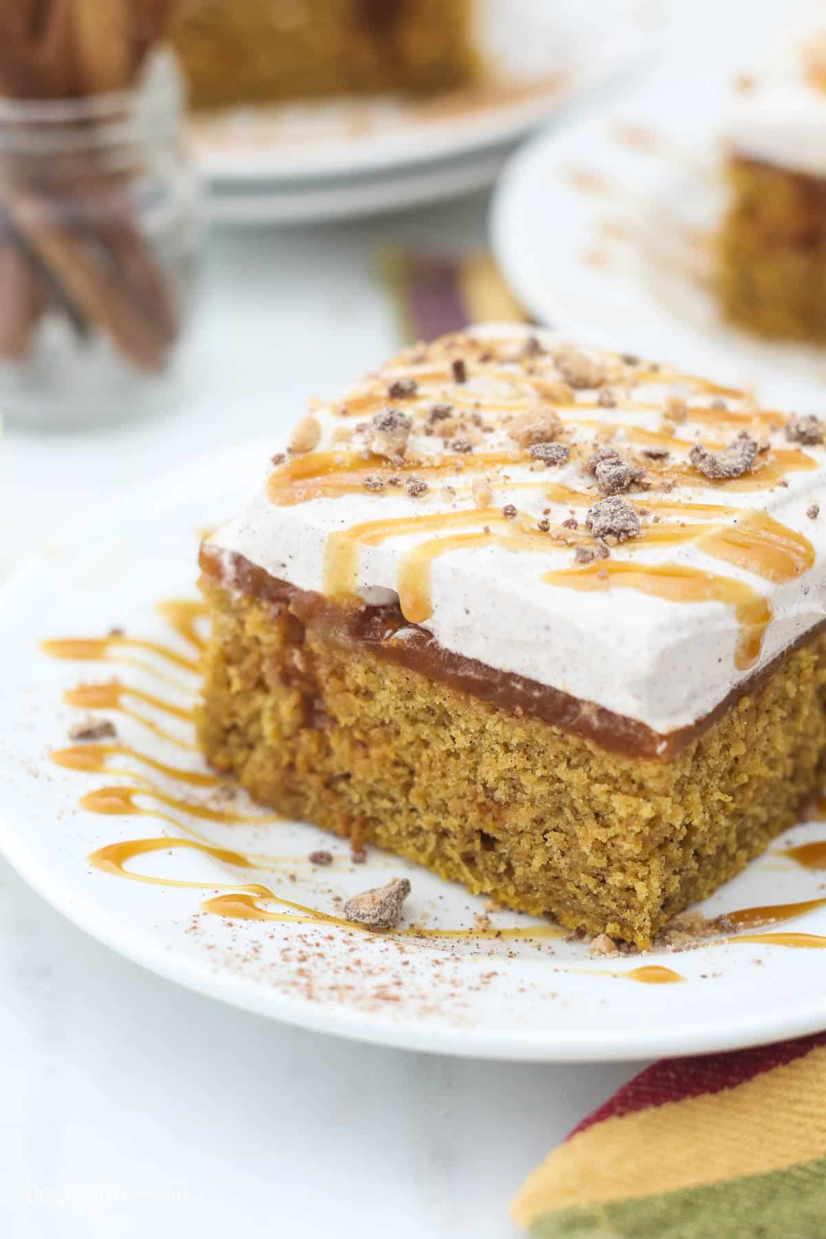An overhead shot of a slice of pumpkin cake showing the caramel drizzle and crushed toffee on top
