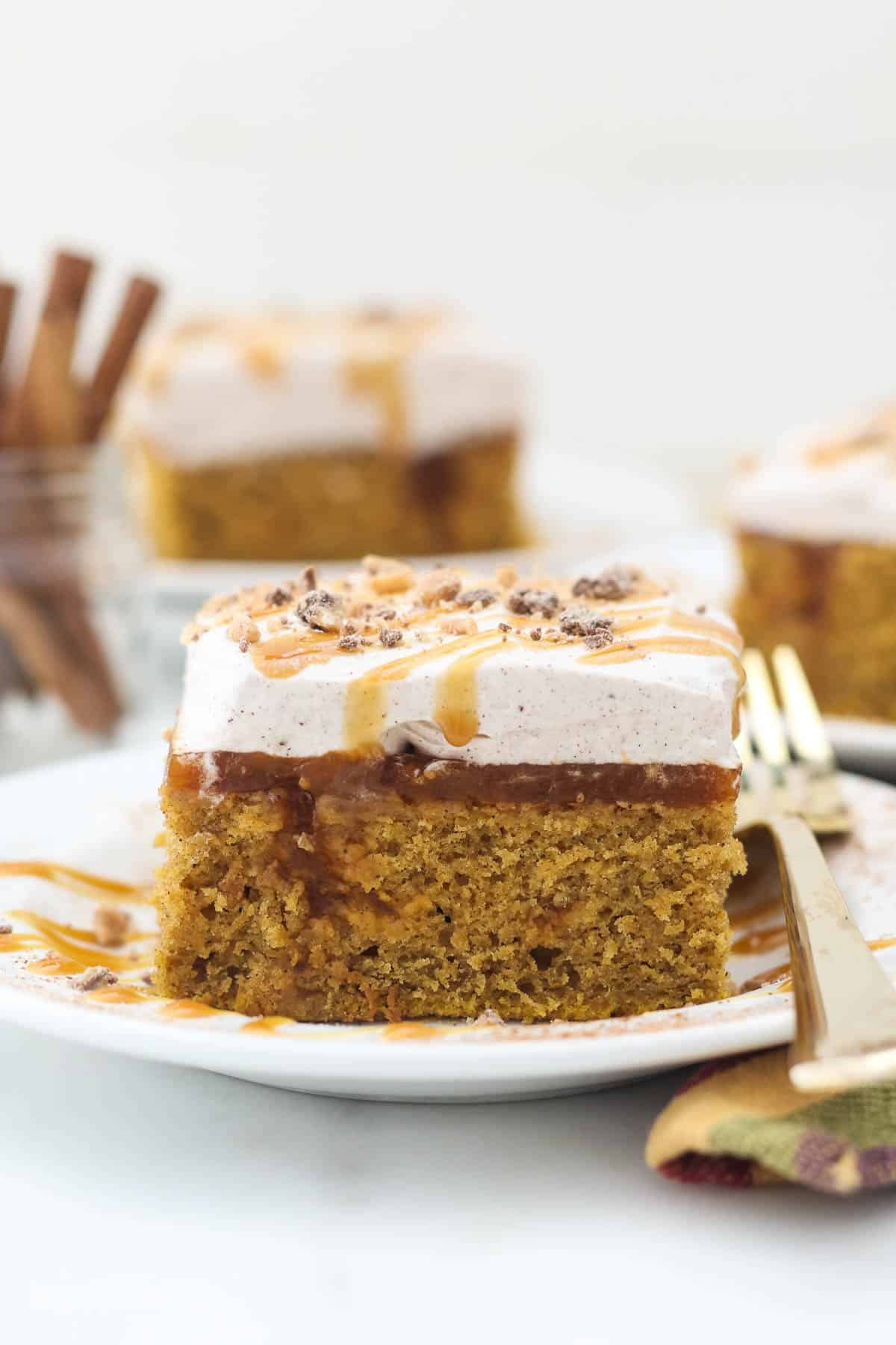 A head on shot of a slice of pumpkin poke cake showing the layers of the cake, and a gold fork laying on the white plate