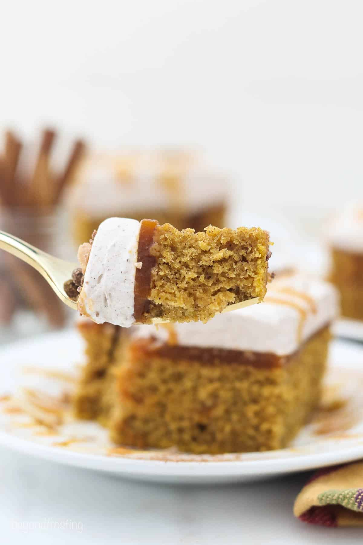 A gold fork with a big bite of cake on it showing the 3 layers of cake, pudding and whipped cream.