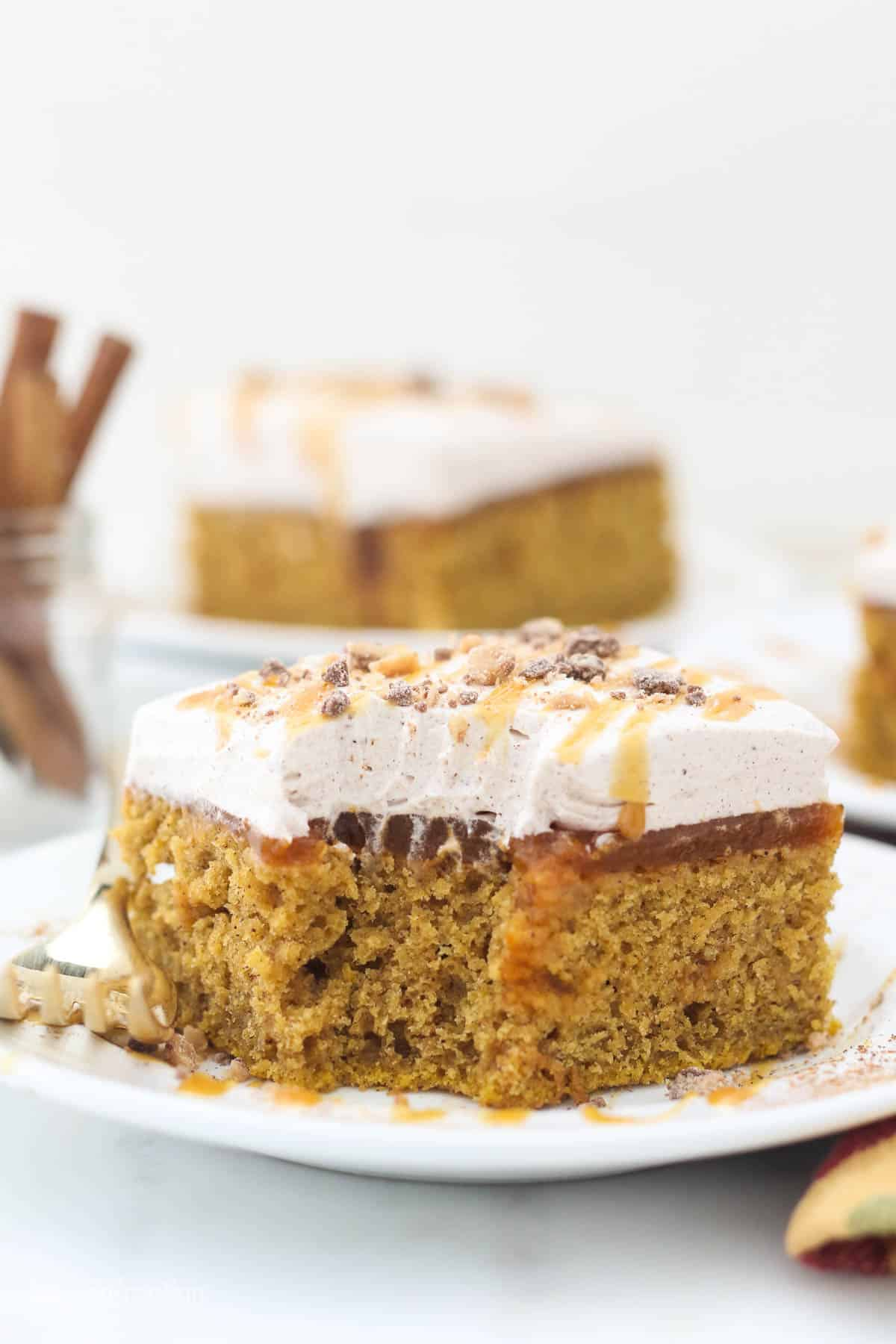 A pretty slice of pumpkin cake with a big bite missing, showing the inside of the cake.