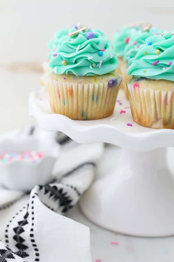 A small white cake stand with gorgeous funfetti cupcakes is draped with a white and black decorative napkin