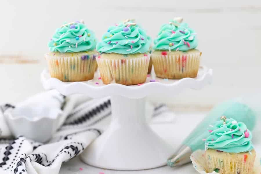 A pretty white cake stand with a ruffled edge is loaded with funfetti cupcake, and draped with a white and black decorative napkin