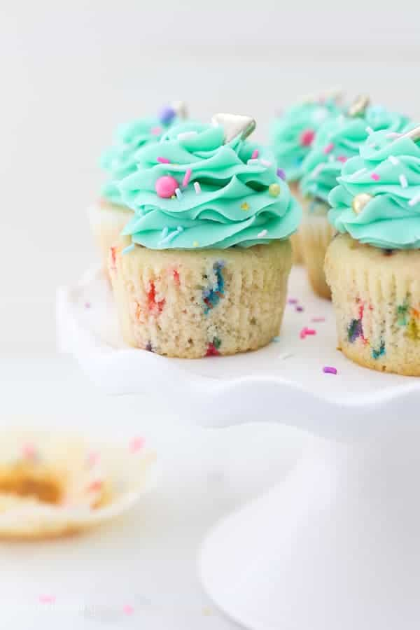 A white ruffled cake stand with funfetti cupcakes with a teal buttercream. The cupcakes are unwrapped.