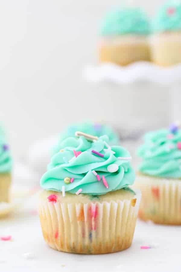 A beautiful cupcake loaded with sprinkles and frosted with a teal buttercream that is also garnished with sprinkles
