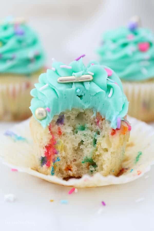 A beautiful funfetti cupcake with a bite taken out of it showing you the inside of the cupcake