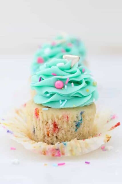 A gorgeous funfetti cupcake with the wrapper pulled down and frosted with a light teal color frosting and garnished with colorful sprinkles