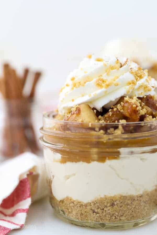 A close up shot of some mini jars of apple pie cheesecake showing the various layers of the dessert