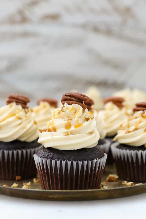 a pretty chocolate cupcake topped with a buttercream swirl and it's dripping with caramel and there's a pecan on top
