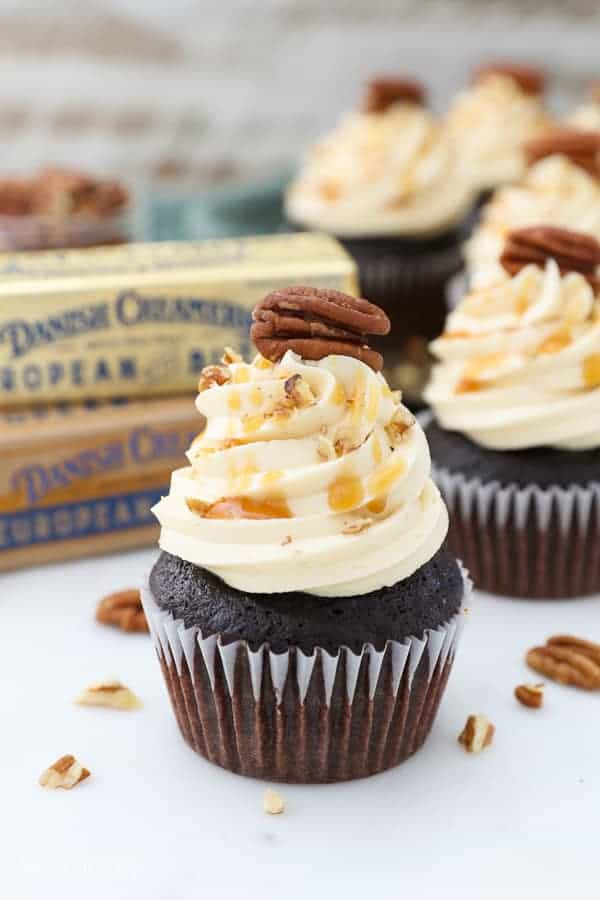 A Chocolate Turtle cupcakes dripping with caramel and e pecan on top.
