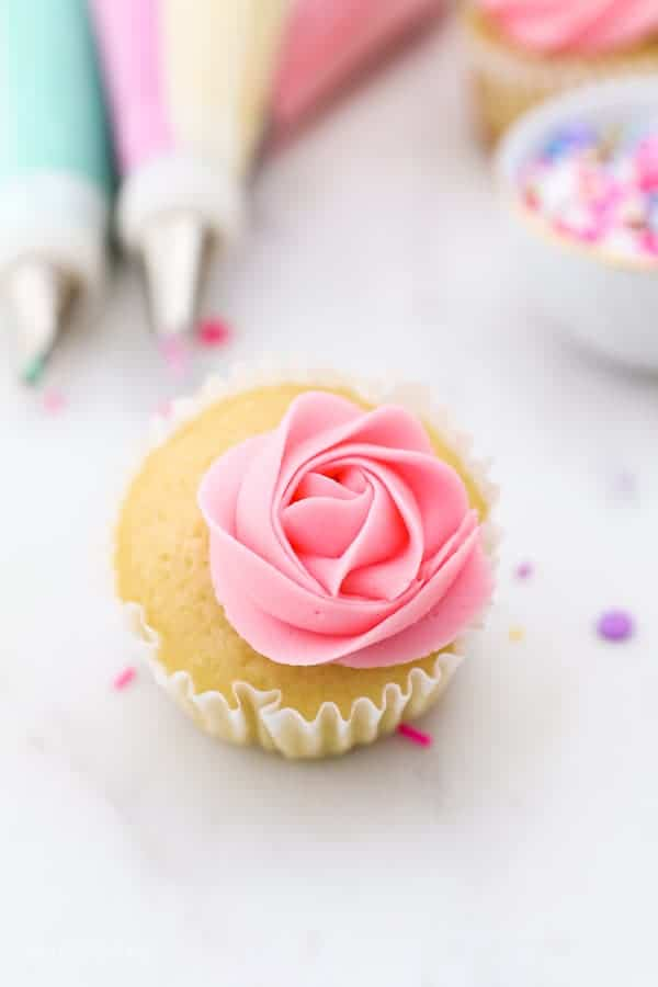 A vanilla cupcake with a pink rose
